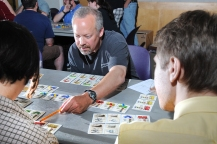 Patrick Rael, center, explains how to play Iron Horses, a game he invented, to Peter Selmayr of Brunswick, right, and Kori Handwerker of Brunswick at the Board Gamers Meetup at the Curtis Memorial Library in Brunswick recently.